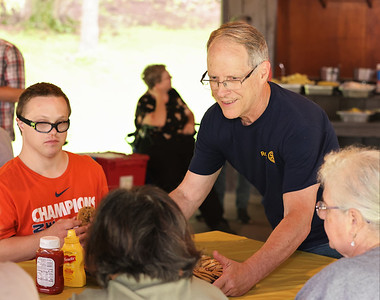 Rotary Club of Rich-Mar volunteer Chuck Berry hands out cookies to adults with disabilities from ARC at the Rotary's annual hot dog bar-b-que at Butler Memorial Park Wednesday. Seb Foltz/Butler Eagle  08/11/21