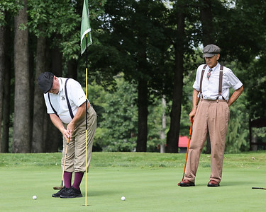 Jim Wally Koss watches Greg Smith putt on hole 6 at Foxwoods during Friday's hickory stick golf Tournament. Seb Foltz/Butler Eagle 08/13/21