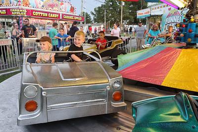 Evalina Steinhiser, 2, and Kayson Maskal, 5, ride the car carousel at the Saxonburg Carnival Thursday night. Seb Foltz/Butler Eagle 08/19/21