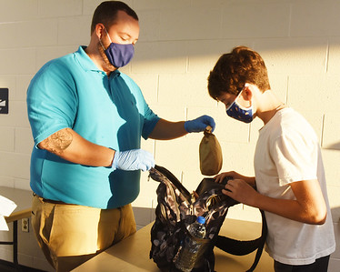Harold Aughton/Butler Eagle: Adam Benson, a 7th/8th grade technology teacher at Mars Middle School checks backpacks prior to students walking through the metal detectors during the first day of school, Tuesday, September 08, 2020.