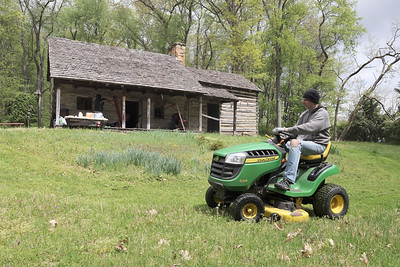 Butler Historical Society volunteer Randy Kruger mows the lawn around Cooper Cabin in Cabot Saturday. Historical Society volunteers spent the day working to clean up and restory the 1800s era cabin. Members hope to have the site back open to vistitors later this year. Seb Foltz/Butler Eagle 05/08/21