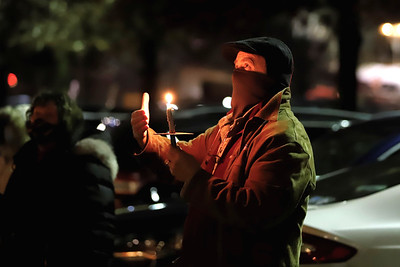Pastor John Silbert of the Covenant Presbyterian Church in Butler tends to his candle at Tuesday night's prayer vigil outside of Butler Memorial Hospital. Seb Foltz/Butler Eagle 12/22/20