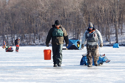 Tyler Rupert(left) and Adam Daubenspeck haul in their gear during Saturday's ice fishing tournament on Moraine State Park's Lake Arthur. Seb Foltz/Butler Eagle 02/06/21