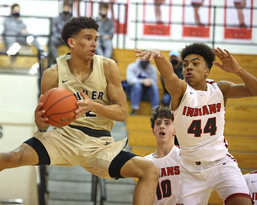 Butler's Devin Carney fakes to the hoop and passes outside against North Hills' Royce Parham in Saturday's road win. Seb Foltz/Butler Eagle 02/13/21