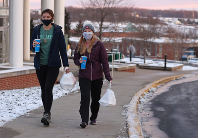 First-year students Alea Burkholder(left, freshman) and Mary Zipfel (sophmore by credit, first year student) walk through campus after picking up dinner at the Boozel Dining Hall Tuesday. The facility remains take-out only due to COVID policy. Seb Foltz/Butler Eagle 01/20/21
