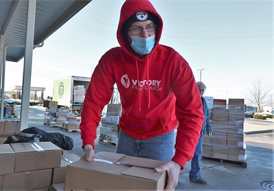 Joel Slowikowski of Victory Family Church lifts a box of food during Tuesday's drive-up church food distribution. Seb Foltz/Butler Eagle 01/19/20