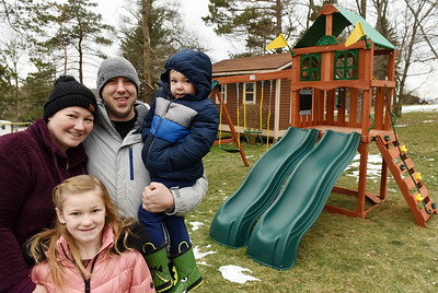 From left, Kimberly, Natalie, 7, Matthew, and Jackson, 3, Karns of Muddy Creek Twp. received a new swing set for Christmas complitments of Lowe's employees in Butler. Harold Aughton/Butler Eagle.