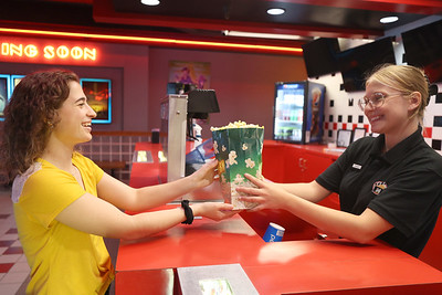 Grace Sybert, 19, hands a bag of popcorn to Chalee Durand, 21, at the soft opening of  Moraine Pointe Cinemas Friday. Seb Foltz/Butler Eagle 07/9/21  (EDITORS NOTE: Posed)