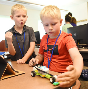 Ben Mason, 6, of Connoquenessing Twp. reacts to the robotic race car that he and his partner, Andrew Rock, 7, of Center Twp. they built during the Kids on Campus program at Butler County Community College Wednesday afternoon. Harold Aughton/Butler Eagle