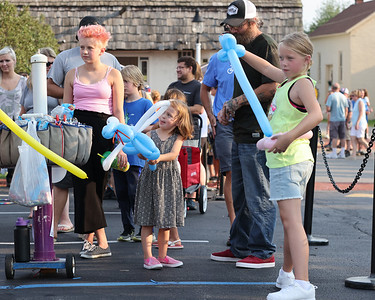 Lillian Florentine, 11, draws her balloon sword with her sisters  Rose,3, and Isabella, 11, at Saxonburg's Mingle on Main Thursday. Seb Foltz/Butler Eagle 07/15/21