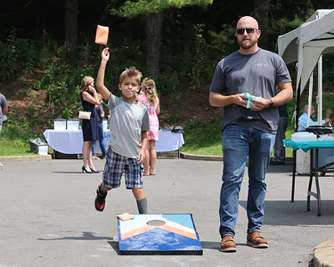 Nick Paff, 8, throws a bean bag in a game of cornhole with Garret English at the 50th anniversary of the Gaiser Center party Wednesday. Seb Foltz/Butler Eagle 07/21/21