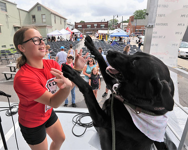 Isabella Annarumo, 12, and her dog Gracie,8, show off their trick competition winning high five in front of family after the Zelienople Horse Trading Days' dog show Saturday. Seb Foltz/Butler Eagle 07/17/21