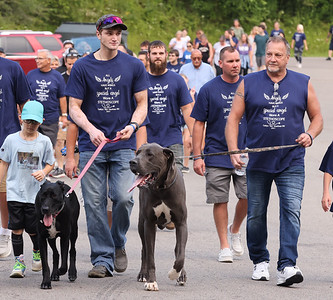 Caitlyn Kaufman's dog Zeus(right) and father Rick Kaufman lead a walk in her memory with her brother Tyler and his dog Mia Saturday at Butler Memorial Park. Kaufman was shot and killed while driving to work in Tennesee in December of 2020, in an alleged road rage incident. Friends and family gathered for a walk and service in her honor. Seb Foltz/Butler Eagle 07/24/21