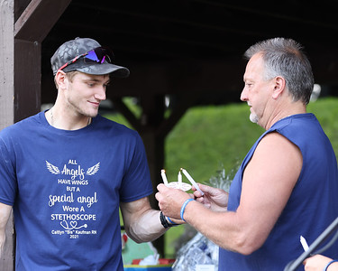 Caitlyn Kaufman's brother Tyler and father Rick Kaufman light candles during a service honoring Caitlyn at Butler's Memorial Park Saturday. Kaufman was shot and killed while driving to work in Tennesee in December of 2020, in an alleged road rage incident. Seb Foltz/Butler Eagle 07/24/21