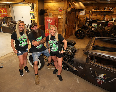 """After Hours Tatoo Studio and Social Club Barbershop co-owner John Podolak (center) and staff members and car show organizers Natasha Spreng (left) and Katie Hill     stand in Podolak's garage with four of his """"ratrod' custom cars. Two will be among cars  featured at this weekend's Mars Rumble car show. Podolak and his shops host the event now in its second year. Seb Foltz/Butler Eagle 07/28/21"""
