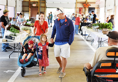 Tim and Laura Wach of Middlesex did a little shopping with their children Henry, 1 1/2, and Josie, 4, Saturday morning at the Butler Farmers Market. Harold Aughton/Butler Eagle.