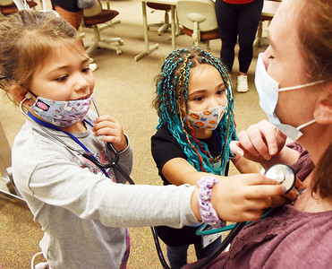 Sophia Adachi,5, and Libbie McCollough,5, had the opportunity to test out a stethoscope on Julia Carney, assistant dean of nursing  during the Super Hero's activity at Kids on Campus summer program sponsored by the Butler County Community College Tuesday morning. Harold Aughton/Butler Eagle.