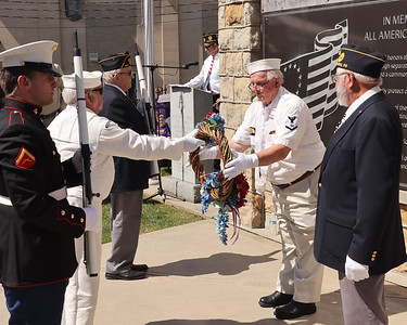 Navy veteran Ron Huff hands a wreath to fellow veteran Chuck Hetrick to be placed on the war memorial in Chicora during Memorial Day ceremonies Monday. Seb Foltz/Butler Eagle 05/31/21