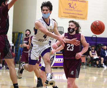 Karn City's Chase Beighley dishes a no-look pass in front of the hoop in Thursday's home playoff win against Ridgway. Seb Foltz/Butler Eagle 03/11/21