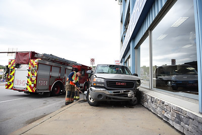 Emergency crews clean up damage after a pickup truccrashed into the stone facade of the 100-year-old Butler County Ford building located at 400 South Main Street in Butler around  April 28, 2021. According to Butler City  police,the driver of the northbound gray GMC Sierra dropped his cigarette and  lost control when he leaned over to retrieve it.  Lauryn Halahurich/Butler Eagle