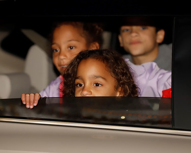 Willow Anderson, 6, peaks over her car window to talk with Santa at Friday's drive-through Santa's Workshop at Alemeda Park. (Twin sister Lilly and brother Kai, 9, also pictured) Seb Foltz/Butler Eagle