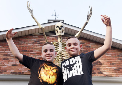 Mason Heltzell, 9, (left) and his brother Matthew,12, have helped decorate their family's home on Winterwood drive in Butler Twp. out with halloween decerations including a 20 ft skelton, graveyard, black cat and other creepy decoration. Harold Aughton/Butler Eagle