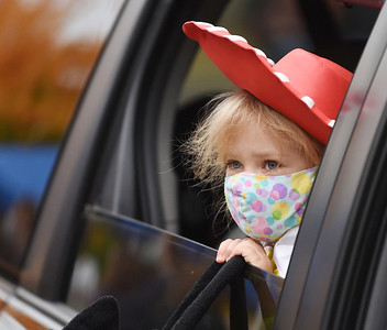Payton Rosswog, 4, holds on tight to her candy bag as her family makes their way through the drive-through trick or treat event at the Mars Elementary School. Harold Aughton/Butler Eagle.