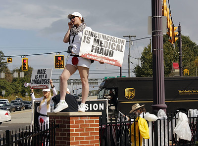 """Dani Alexander, a member of """"Bloodstained Men and Their Friends,"""" holds a sign speaking against male circumcision at a protest in Cranberry. Julia Maruca/Butler Eagle"""