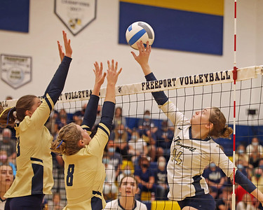 Freeport's Erica Lampus (14) taps the ball over Knoch's  Brynnae Coe (8) and Krystle Ekas (23) in the Yellow Jackets 3-0 home win. Seb Foltz/Butler Eagle 09/14/21