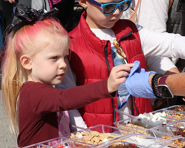 Abigail Cooper, 5, get's a chocolate covered apple wedge to dip in toppings with her brother Dominic Cooper, 8, at Mars Apple Fest Saturday. Seb Foltz/Butler 10/02/21