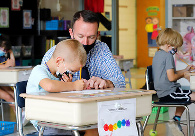 Northwest Elementary School principal helps first grader Carter Tosadori with an assignment Tuesday. Seb Foltz/Butler Eagle 09/08/20