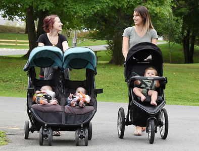 Harold Aughton/Butler Eagle: Former co-workers Michele Anthony of Butler, left, and Chelsea Werth of Butler use to spend their lunch break walking together. Today, the stay-at-home moms recently reconnected and began walking at Alameda Park with their children. Michele pushes a stroller wither her 6-month-old twin boys,  Elias and Tobias, while Chelsea walks her 10-month-old son, Eric.
