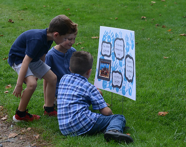 Jesse, 6, Adam, 7, and Maxwell, 7, of Connoquenessing Valley Elementary School in Zelienople sit by a sign made by students at the school for the Peace Day ceremony on Tuesday. Julia Maruca/Butler Eagle