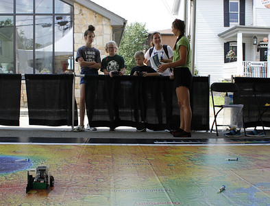 Kayleigh (13), Ashley (11), AJ (8) and Trish DeVincentis, of Newcastle, learn to drive a robot on a giant map of Mars with Mars Robotics member Lindsey Gourash. Julia Maruca/Butler Eagle