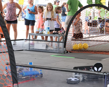 Chloe Zwigart, 9, of Mars, plays robot soccer against her sister Katie, 11, (not pictured) at the Mars Robotics Association tent at Mars Exploration Celebration Saturday. Chloe beat her sister 3-0. Seb Foltz/Butler Eagle 08/28/21