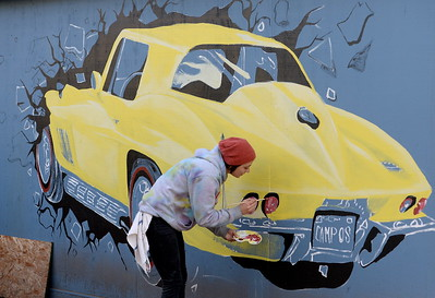Artist Katee Cavallaro of Chico, works on a mural of a 1967 Corvette Stingray on the side of a building on Pine Street owned by Mike Campos in Chico, Calif. Friday Feb. 5, 2016. The garage was struck by a vehicle in October and once had a different mural on it so the owner decided to replace the mural after repairs to the structure were completed. (Bill Husa -- Enterprise-Record)