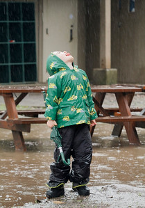 Aiden Brun, 5, looks up to the sky for a drink of water as rain pours and puddles gather around him Wednesday, January 6, 2016 in Chico, Calif. (Emily Bertolino -- Enterprise-Record)