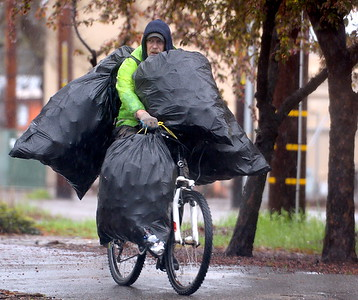 A man rides a bicycle with bags of cans along Park Ave. in Chico, Calif. Fri. March 11, 2016. (Bill Husa -- Enterprise-Record)