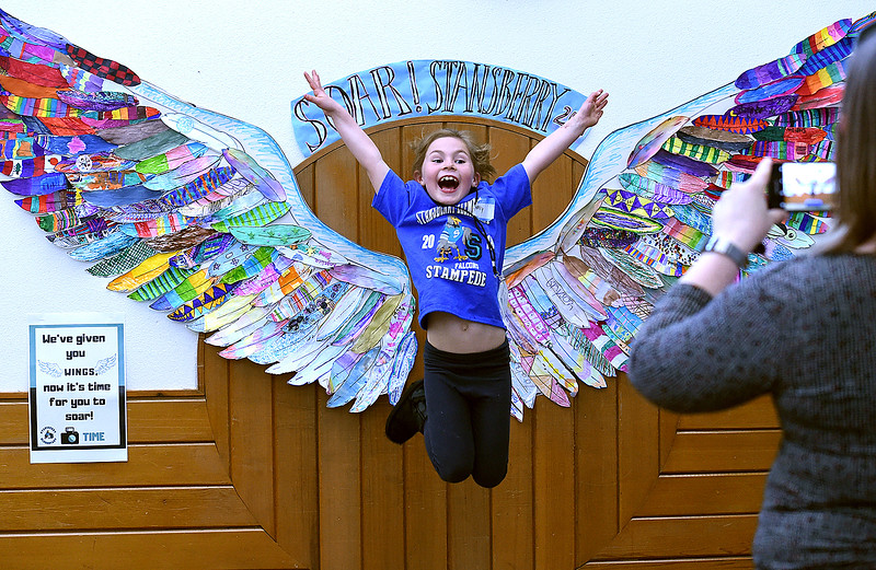 "Stansberry Elementary School second-grader Molly Jacobs, 8, jumps in the air with her arms spread like wings and sings ""I believe I can fly"" as her mom, Erin Jacobs, right, takes a photo of her near a set of wings at the school Thursday, April 25, 2019, during an event to celebrate 38 years of education at the neighborhood school that will close at the end of this school year. Students at the school each made a feather to create the wings and a sign next to it reads ""We've given you wings, now it's time for you to soar!"" (Photo by Jenny Sparks/Loveland Reporter-Herald)"