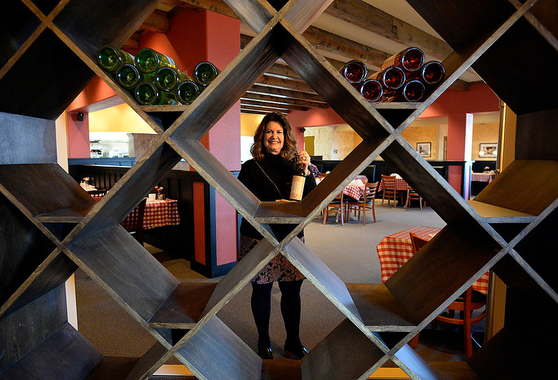 "Annie Vick, owner of the new Pinocchios Incredible Italian restaurant at 1455 Rocky Mountain Ave. in Loveland, poses for a photo framed by the wine rack on Thursday, Feb. 21, 2019. The new restaurant, housed in the former Johnny Carino's building, opened on Valentine's Day. It's the fifth location for the chain, which is based in Longmont. In 2003, recently divorced single mom Annie needed a way to support her three children. She borrowed $15,000 from her mom and started a restaurant in ""an old beat-up location on Main Street.""  (Photo by Jenny Sparks/Loveland Reporter-Herald)"