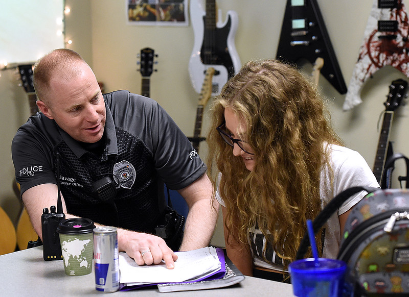 Loveland Police Officer and Ferguson High School Resource Officer Doug Savage helps student Logan Bretsch during music class Tuesday, April 16, 2019, at the school in Loveland. Savage was a music teacher before becoming a police officer.  (Photo by Jenny Sparks/Loveland Reporter-Herald)