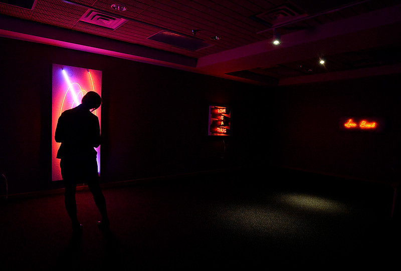 "Marina Babcock, a volunteer at the Loveland Museum Gallery, is silhouetted Friday, Feb. 1, 2019, by a neon piece titled ""That is All You Need to Know"" by artist Scott Young while checking out his Love is a Thug exhibit at the museum in downtown Loveland.    (Photo by Jenny Sparks/Loveland Reporter-Herald)"
