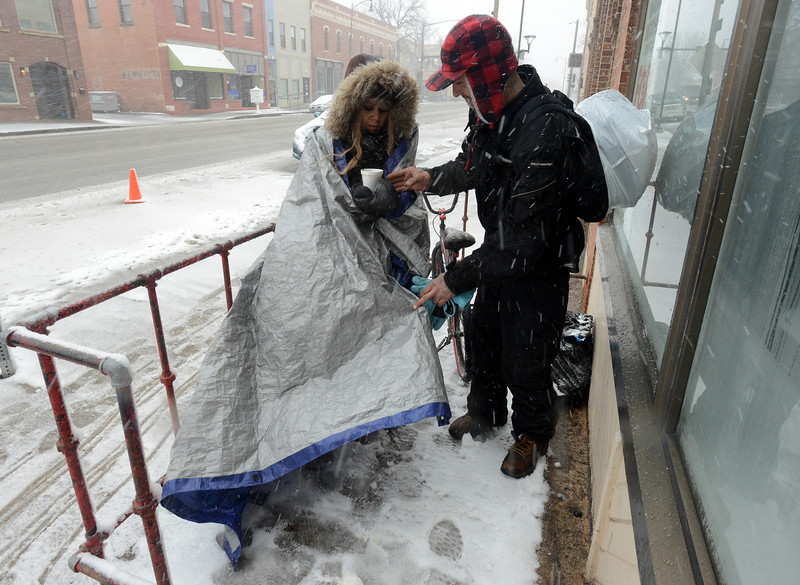 Anthony Johnson, right, helps Yvonne Martinez wrap a tarp around herself against the blowing snow Wednesday, March 13, 2019, outside Front Porch Ministry in downtown Loveland, where they had just finished lunch. The homeless friends were getting ready to walk to 137 Homeless Connection to keep warm, before heading back to their camp for the night. (Photo by Craig Young / Loveland Reporter-Herald)