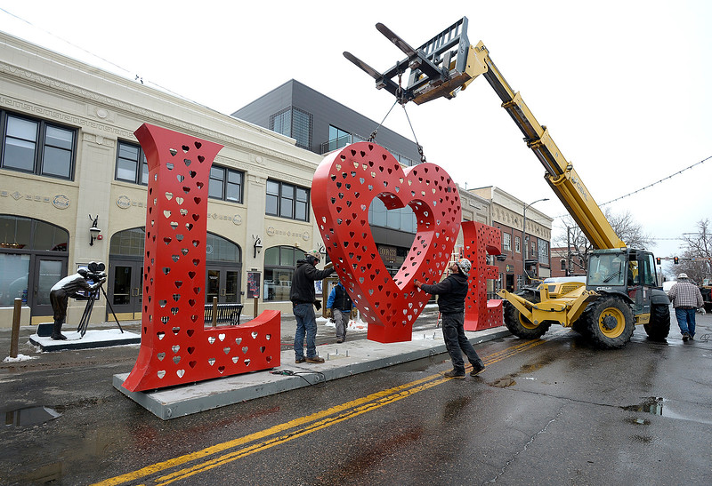 """LPR Construction employees Cody Mai, left, and Matthew Anderson steady the heart shaped """"O"""" of the Love Locks sculpture as a forklift moves it to the base Thursday, Feb. 7, 2019, in front of the Rialto Theater in preparation for this weekend's Loveland Sweetheart Fesitval:Love Locks Lights in downtown Loveland. LPR Construction donated their time to move the sculpture from the Chamber of Commere to downtown. (Photo by Jenny Sparks/Loveland Reporter-Herald)"""