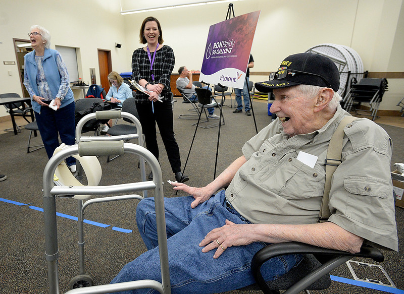 Ron Reidy smiles as he is honored for donating nearly 50 gallons of blood by Liz Lambert, center, marketing and communications manager for Vitalant, formerly Bonfils Blood Center, on Tuesday, April 9, 2019, at the Loveland Police and Court Buidling in Loveland. His wife, Carolyn Vivrina, far left, is all smiles as he is honored. Reidy came for his 400th donation, which would equal 50 gallons) but he was unable to donate for medical reasons. After finding out he couldn't donate Tuesday his first question was when could he come back to donate.   (Photo by Jenny Sparks/Loveland Reporter-Herald)
