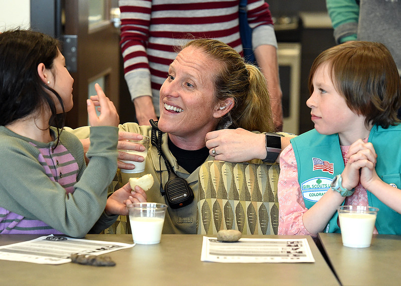 Larimer County Department of Natural Resources District Manager Chris Fleming, center, chats with girls scouts Taylor Santistevan, 8, left, and Kinsley Bau, 9, while the three eat cookies and milk Friday, April 5, 2019, at the Horsetooth Area Information Center west of Fort Collins. A group of the Girl Scouts was impressed with Larimer County park rangers when they camped at Pinewood last summer so they wanted bring them some Girl Scout Cookies as a thank you.  (Photo by Jenny Sparks/Loveland Reporter-Herald)