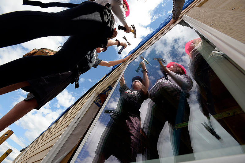 Loveland High School students Shawn Rowlatt, 15, left, Emma Manwell, 15, center, and Amelia Skoglund, 16, are reflected in a window as they stand on scaffolding while nailing siding on the outside of a house Wednesday, April 24, 2019, during their Geometry in Construction class at the school in Loveland. Students in the class are building a Loveland Habitat for Humanity home.  (photo by Jenny Sparks/Loveland Reporter-Herald)