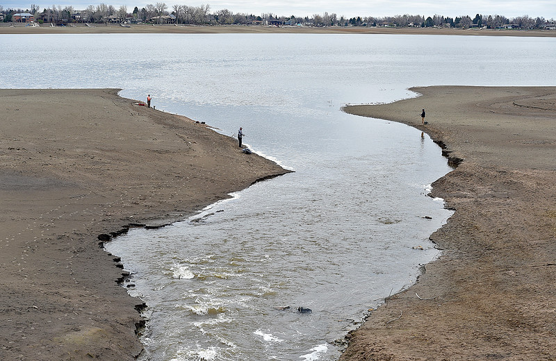 Ryan Huszar, left back, Tommy Fowler, left, and Craig Toler, right, fish near the inlet to Lake Loveland on Monday, April 22, 2019, on the south shore. After many months of the lake being at low levels the water near the inlet is flowing in fast and filling up the lake.  (Photo by Jenny Sparks/Loveland Reporter-Herald)