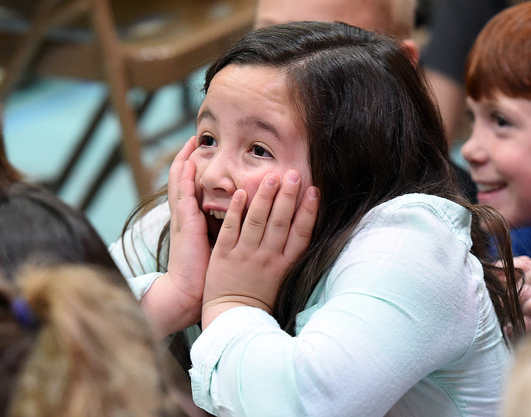 """Ella Bebo, a Van Buren Elementary School second-grader, reacts Thursday, April 25, 2019, as Perry Conway shows kids a boa constrictor snake and tells them he once saw one of those snakes eat a bat. Conway did a presentation about bats at Namaqua Elementary School for students from there and Van Buren Elementary School trying to replace folklore with science about bats and said """"I want to give a positive impression on an animal that is largely misunderstood."""" Because the stress would be unhealthy for bats he did not bring a live bat but he brought animals that he has seen eat bats like the boa constrictor, a peregrine falcon and a cane toad to show the kids. (Photo by Jenny Sparks/Loveland Reporter-Herald)"""