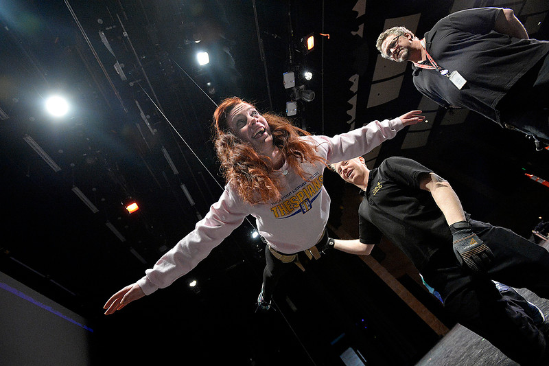 Rachel Miller, a Mountain View High School student who plays Ariel in their production of The Little Mermaid, tries to hold her body in a horizontal position while learning to fly using a safetly harness and cables on Wednesday, Feb. 20, 2019, at the school's auditorium in Loveland. Jason Whicker, center right, president of On the Fly Productions, gives Miller some tips as Thomas Kearney, right, Thompson School District Theater and Production manager, watches.  (Photo by Jenny Sparks/Loveland Reporter-Herald)